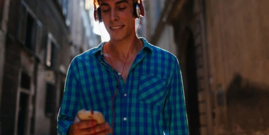 Man Walking Through The City Listening Music With Mobile Phone
