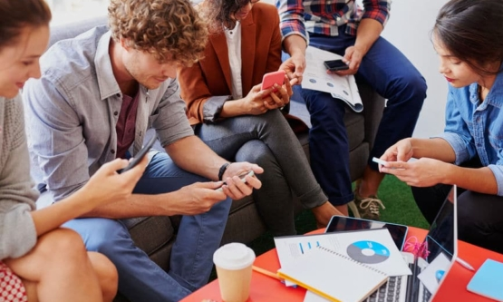 Young Professionals All Using Their Smartphones