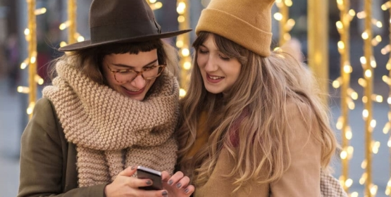 Two Young Women Using A Phone On The Street