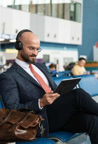 Glad businessman using tablet in lounge room
